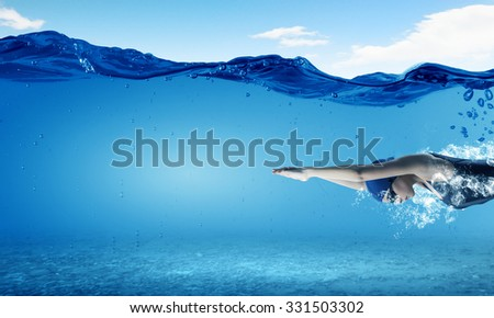 Young woman swimmer in cap and glasses under water - stock photo