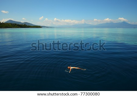 Young woman swimming by coral reef in transparent tropical sea. Bunaken island. Indonesia