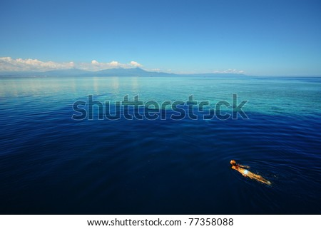 Young woman swimming by coral reef in transparent tropical sea. Bunaken island. Indonesia - stock photo