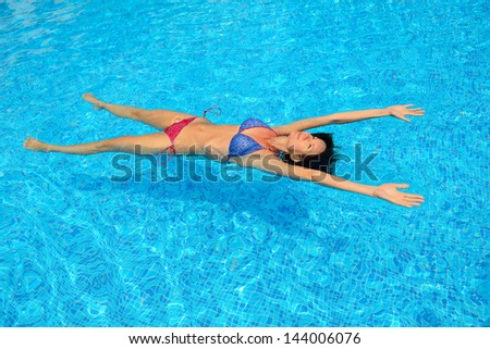 young woman swimming in water pool - stock photo