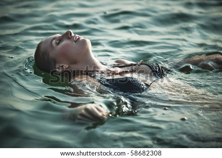 Young woman swimming. Soft green tint. - stock photo