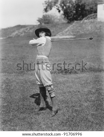 Young woman swinging a golf club on a golf course