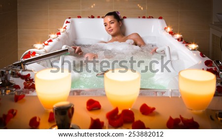 Young woman takes bubble bath with candle.  - stock photo