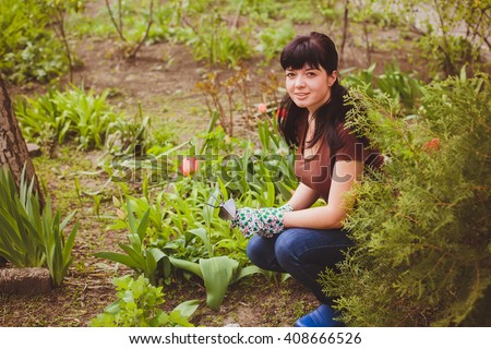 Young woman takes care of the plants and flowers in the garden. Spring garden - stock photo