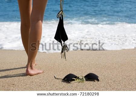 Young woman takes off bikini to swiming in the sea. - stock photo