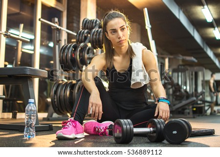 Young woman taking a break in a gym.