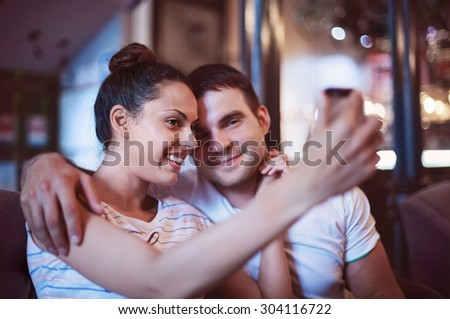 Young woman taking a photo with her mobile phone in a cafe. Happy young couple doing selfie - stock photo