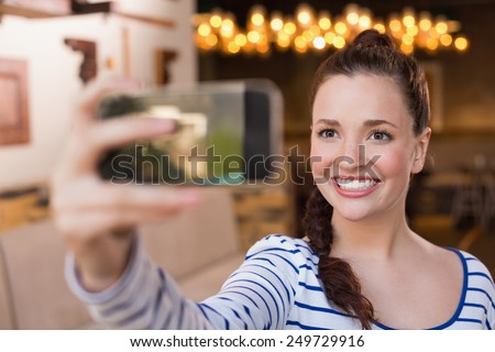Young woman taking a selfie at the cafe - stock photo