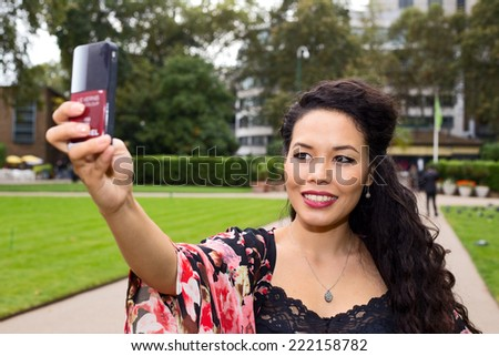young woman taking a selfie in a park.