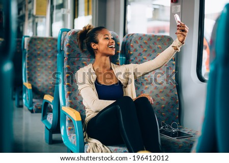 Young woman taking a selfie on train with her phone - stock photo