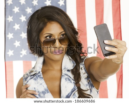 Young woman taking a SELFIE portrait of herself for  social networking with the American Flag behind her.  Lifestyle concept photo. - stock photo