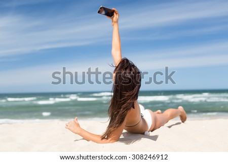 Young woman taking a selfie while relaxing at the beach