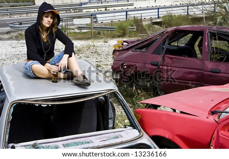 Young woman taking beer in the scrapyard - stock photo