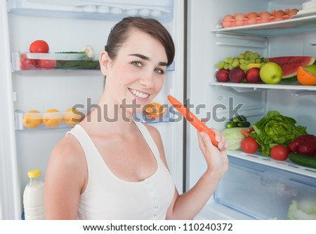 young woman taking carrot juice out of fridge