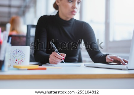 Young woman taking notes from laptop. Female executive working her  desk using laptop and writing notes. - stock photo