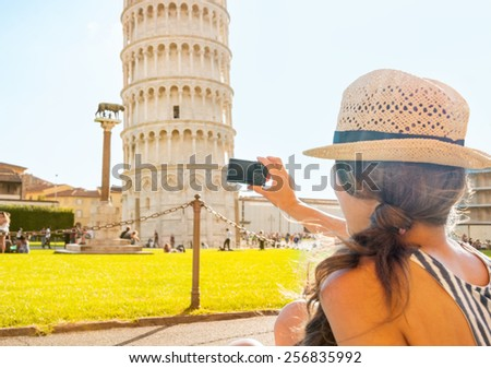 Young woman taking photo of leaning tower of pisa, tuscany, italy. rear view - stock photo