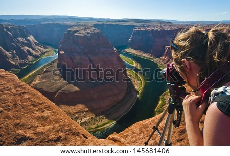 Young woman taking photograph of panoramic view of Horseshoe Bend at Utah, USA - stock photo