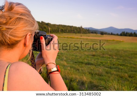 Young woman taking pictures at sunset with a digital camera in Lake Placid area, Adirondack,  Upstate New York.  Photography, adventure, travel vacation, outdoors and life style concept - stock photo