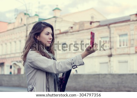 Young woman taking pictures on the smartphone while walking through the streets of the city.