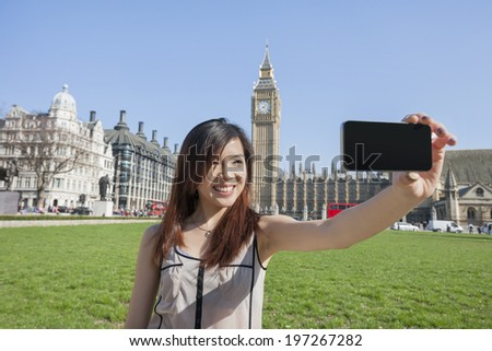 Young woman taking self portrait through smart phone against Big Ben at London; England; UK - stock photo