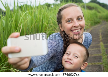 Young woman taking self portrait with her son in a park - stock photo