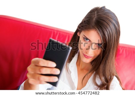 Young woman taking selfie. Beautiful female with confident look on her face holding smart phone. She is sitting on red sofa isolated over white background. - stock photo