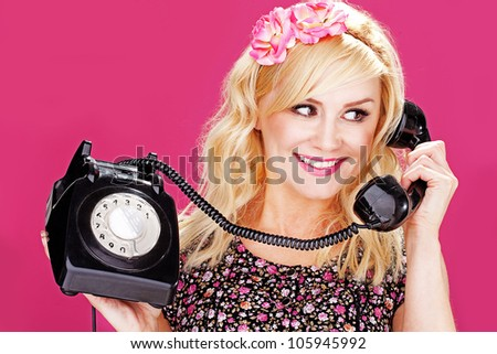 Young woman talking on an old dial up telephone. - stock photo