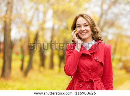 young woman talking on cell phone in the autumn park - stock photo