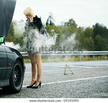 Young woman talking on mobile phone near broken and smoking car - stock photo