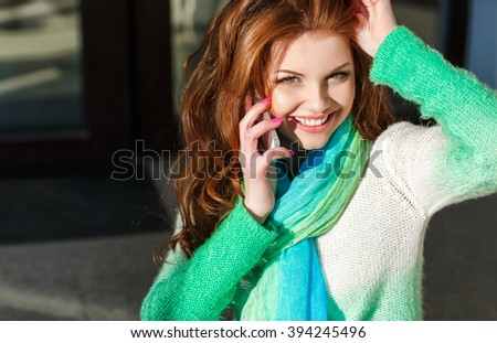 Young woman talking on mobile phone. Young beautiful smiling woman talking on cell phone. Lady talking on the mobile phone outdoor - stock photo