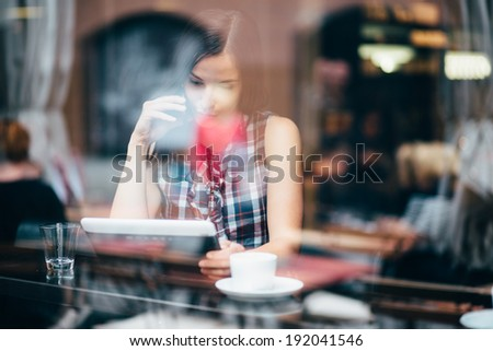 Young woman talking on phone and using tablet computer in coffee shop - stock photo