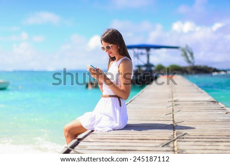 Young woman talking on phone during tropical beach vacation - stock photo