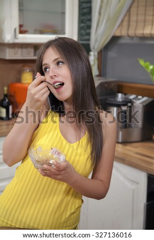 Young woman talking on smart phone while eating ice cream in the kitchen at home.
