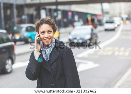 Young woman talking on the phone next to a busy street in London. She is a beautiful mixed race woman on her late twenties. Lifestyle and communications concepts in a urban context. - stock photo