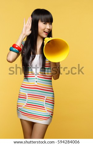 Young woman talking through yellow megaphone, hand to ear