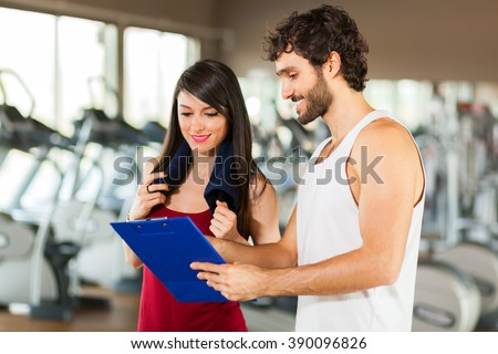 Young woman talking to her fitness trainer in the gym as they consult a clipboard charting her progress