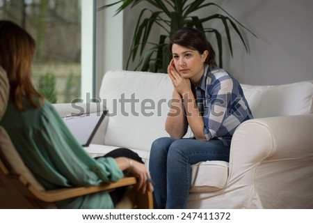 Young woman talking with psychologist about her problems - stock photo