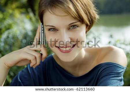 young woman talks outdoors with a cell phone in her hands - stock photo