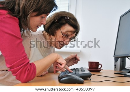 Young woman teaches her grandmother work with computer - senior lifestyle - stock photo