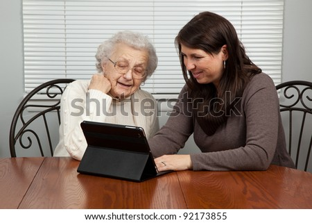 Young Woman Teaching Senior Woman How to Use a Tablet PC - stock photo