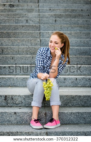 Young woman - teenage girl eating grapes outdoor sitting on stairs - stock photo
