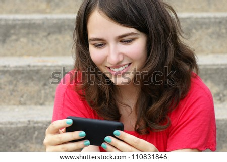 Young woman, teenager girl or student reading text on her cell phone and smiling, perfect for social media, networking or other internet technology. - stock photo