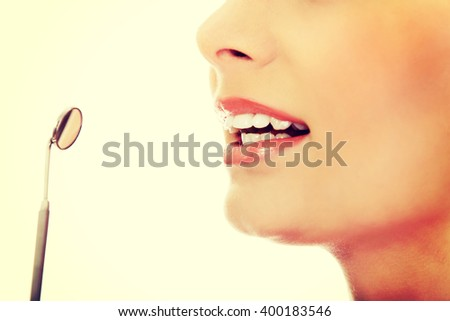 Young woman teeth and a dentist mouth mirror - stock photo