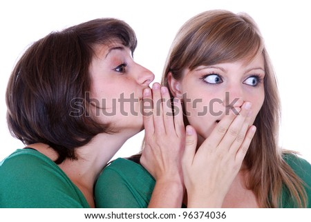 young woman tells her friend a secret
