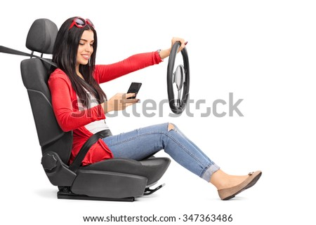 Young woman texting and driving seated on a car seat fastened with a seatbelt isolated on white background - stock photo