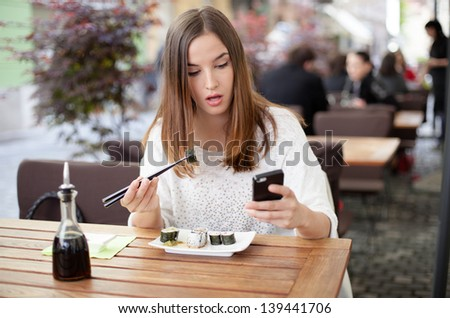 Young woman texting while eating sushi in a restaurant - stock photo