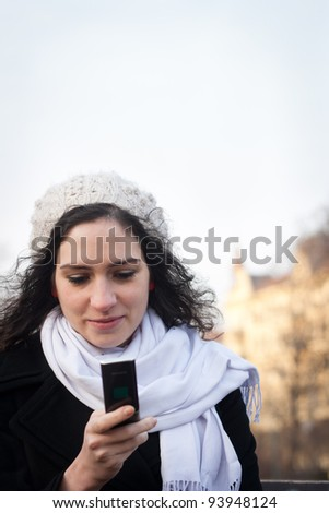 Young woman texting with her phone outdoors on a fall/winter day