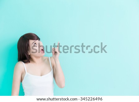 young woman think something isolated on green background, asian beauty - stock photo