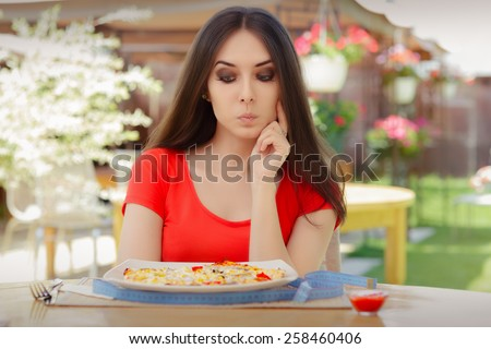 Young Woman Thinking About Eating Pizza on a Diet - Beautiful girl Making Nutrition Decisions in a Restaurant - stock photo