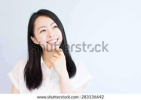 young woman thinking against light blue background - stock photo